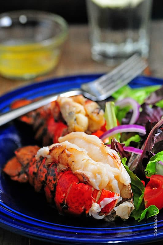 Blue plate containing Smoked Lobster Tail, a side salad and a fork, butter in background for dipping.