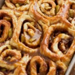 Cinnamon sticky buns topped with caramel and apples in a pan.
