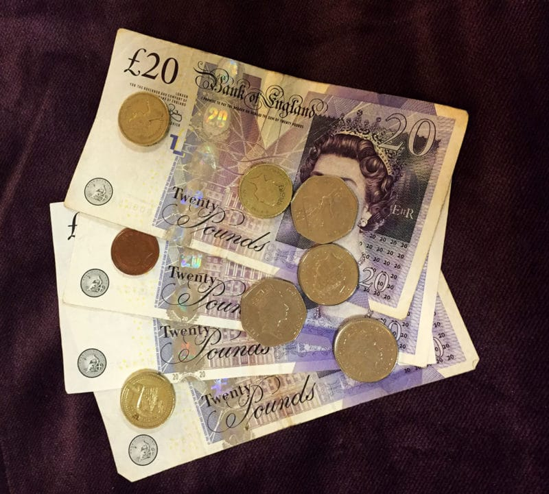 UK pounds and pence sitting on a purple cloth.
