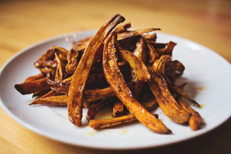 White plate containing a pile of Honey Drizzled Sweet Potato Fries, sitting on a brown table.