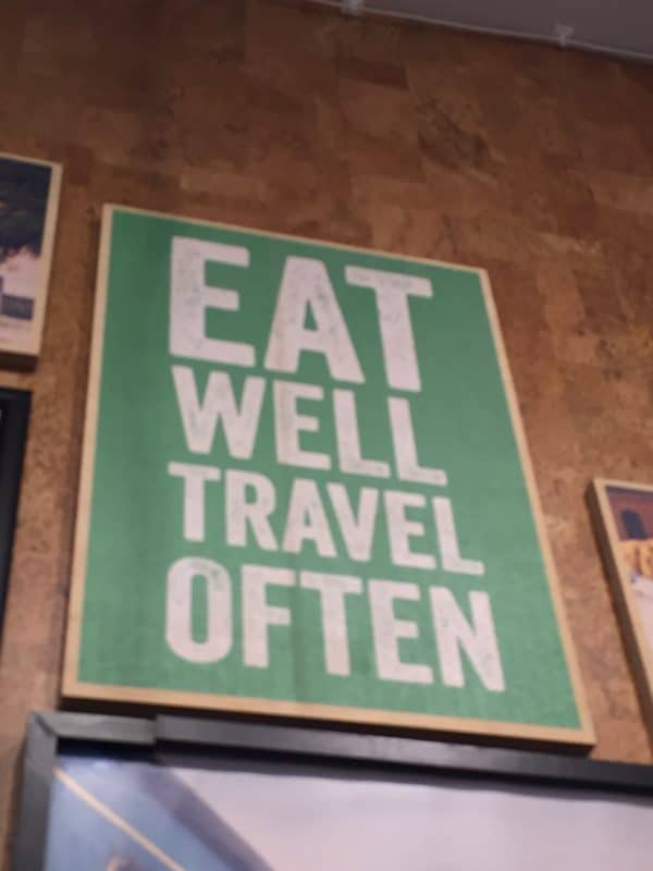"Green sign with white letters reading ""Eat Well, Travel Often""."