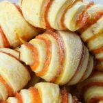 Pumpkin crescent rolls piled on a plate.