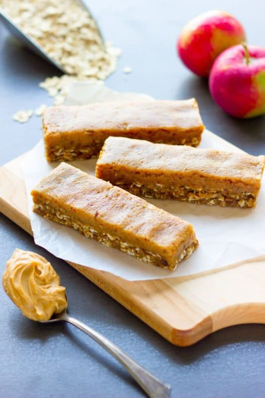A brown cutting board containing 3 No-Bake Caramel Apple Pie Protein Bars with apples, oats and peanut butter on a spoon.