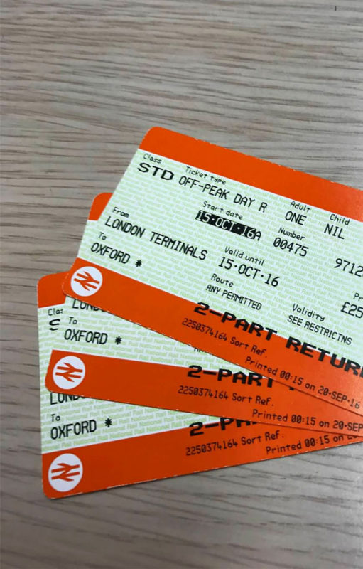 Three train tickets from London to Oxford sitting on a brown table.