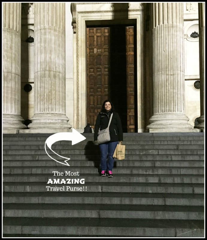 Person standing on gray stairs wearing a cross-travel purse.