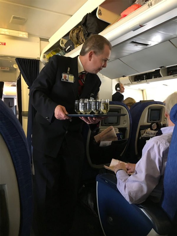 Business Select class on British Airway featuring a flight attendant serving champagne to passengers.
