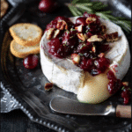 A platter with baked brie topped with cranberries and fresh rosemary, crackers on table.
