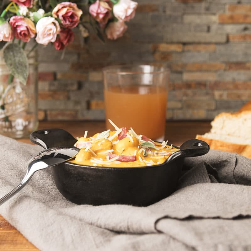 Black bowl containing Gnocchi With Pumpkin, Sage, And Turkey Bacon sitting on a gray napkin, juice , bread and flowers in background.