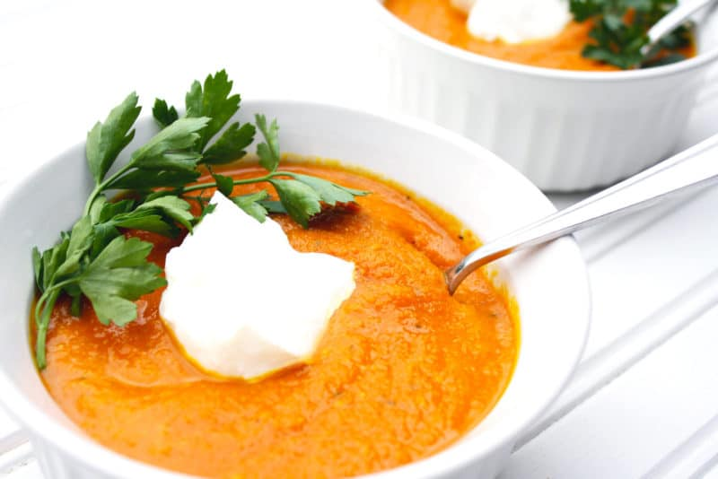 White bowl containing Carrot Turmeric Ginger Soup, topped with sour cream and parsley.
