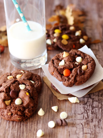 Five Double Chocolate Peanut Butter Cookies sitting on a wooden table next to a glass of milk with a blue straw, white chocolate chips on side.