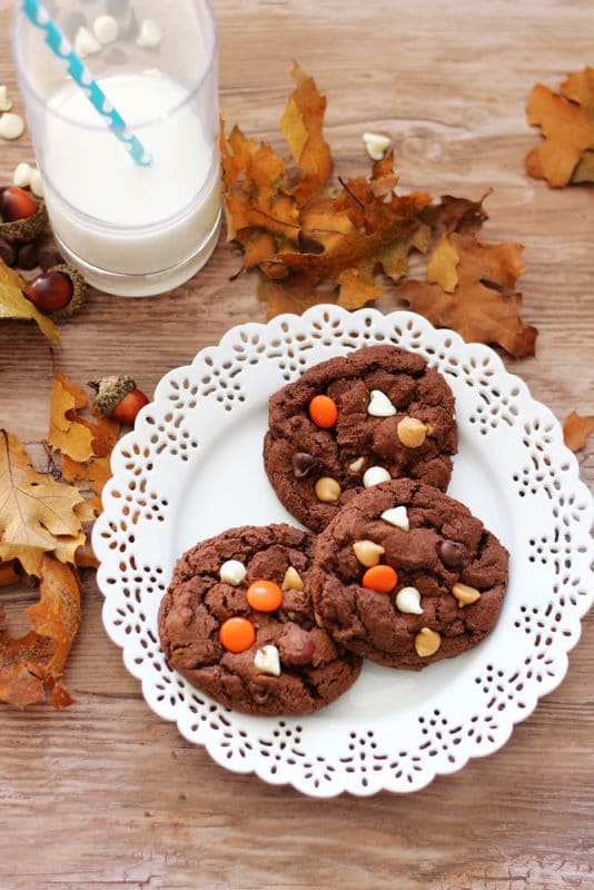 White laced plate containing 3 Double Chocolate Peanut Butter Cookies sitting on a wooden table, a glass of milk on table with fall leaves.