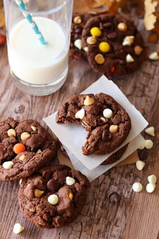 Five Double Chocolate Peanut Butter Cookies with the center cookie missing a bite sitting on a wooden table next to a glass of milk with a blue straw, white chocolate chips on side.
