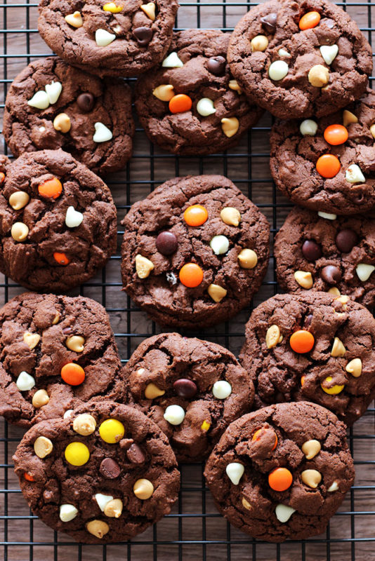 Black wire rack containing a batch of Double Chocolate Peanut Butter Cookies, topped with Reese's Pieces, white chocolate chips and peanut butter chips.