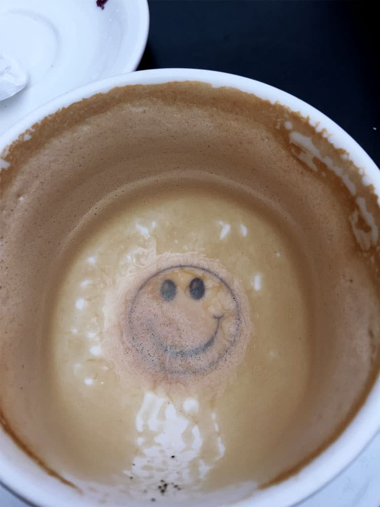 Empty cup of cappuccino showing a smiley face, featured in an article for a gift guide for the traveler.