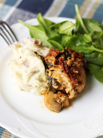White plate containing Instant Pot Garlic Chicken with White Wine & Dijon Mustard Cream Sauce with a side of mashed potatoes and spinach salad.