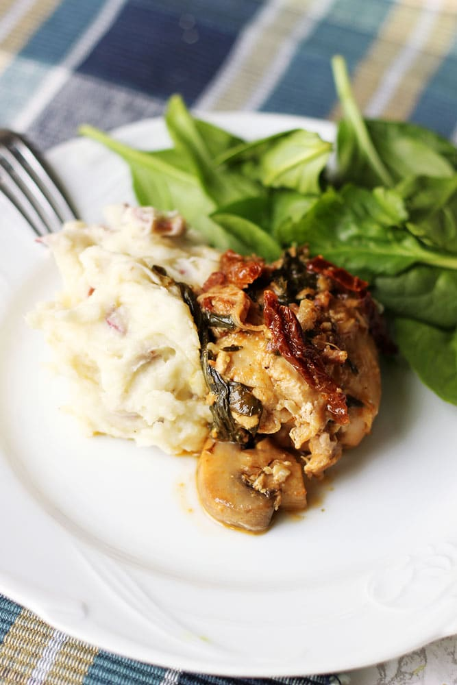 White plate containing Instant Pot tuscan chicken with a side of mashed potatoes and spinach salad.
