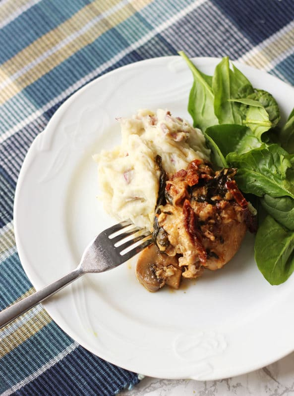 White plate containing Instant Pot Garlic Chicken with White Wine & Dijon Mustard Cream Sauce with a side of mashed potatoes and spinach salad, fork on side of plate.