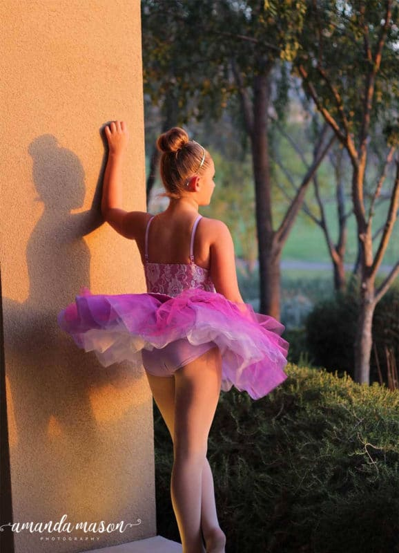 Ballerina looking out into a fairytale wooded forest, shadow on wall.