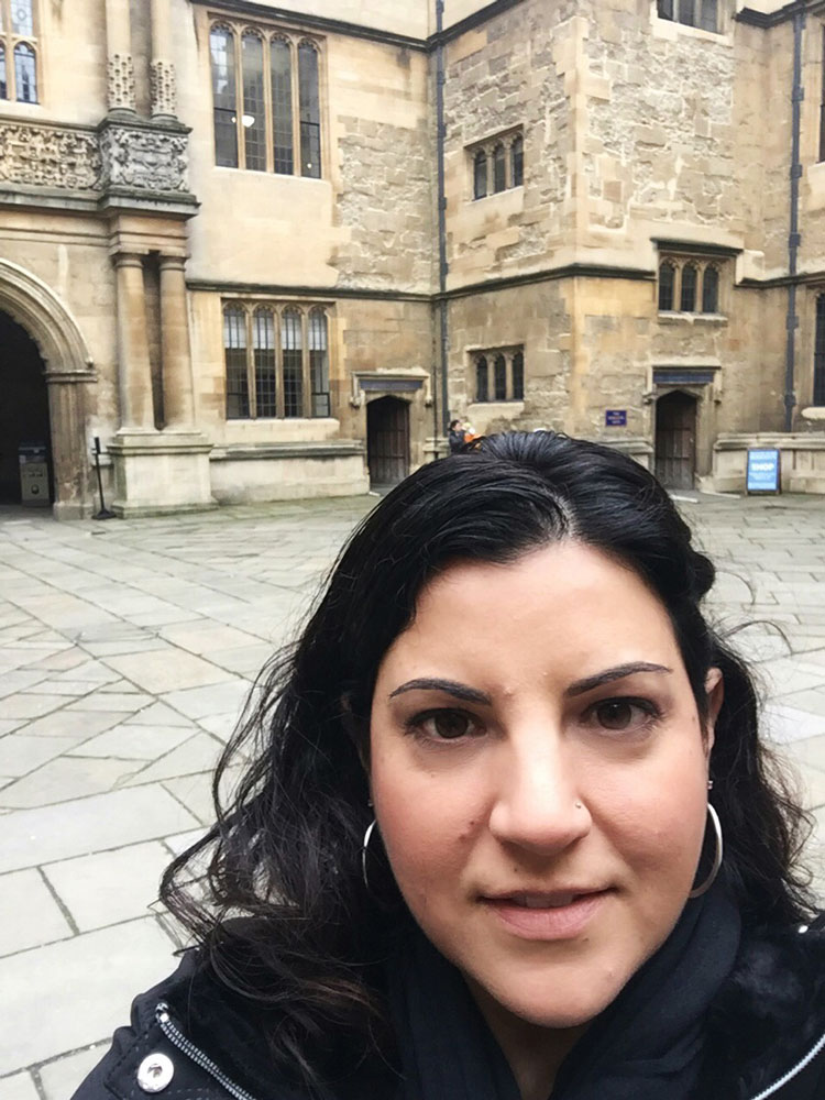 A woman posing in front of the Bodleian Library in the UK.