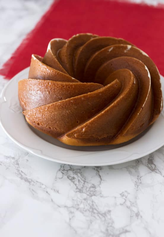 Side view of an Orange Vanilla Bundt Cake sitting on a white plate on a marble table, red tablecloth on table.