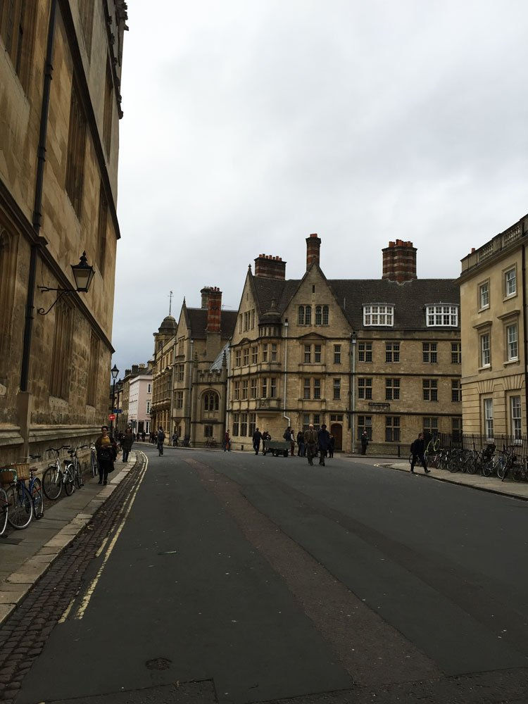 Street in Oxford, UK with historical cafes and buildings along street.