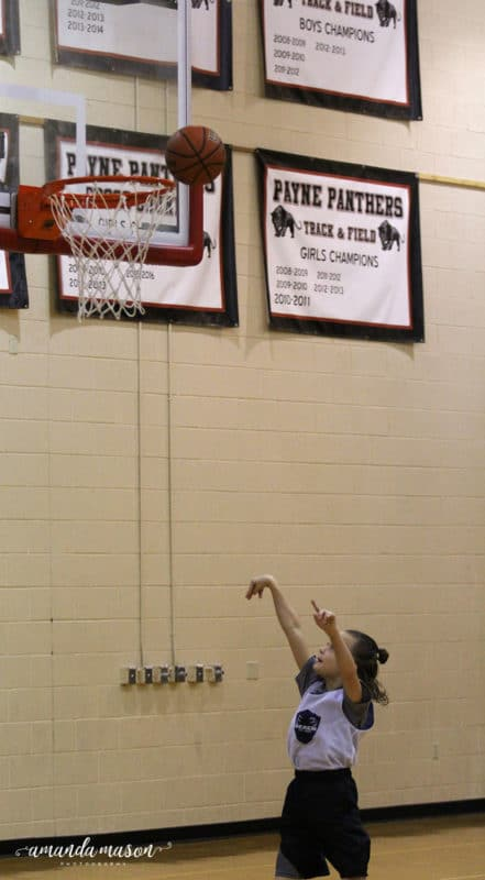 Boy taking a basketball shot into hoop in a gymnasium.