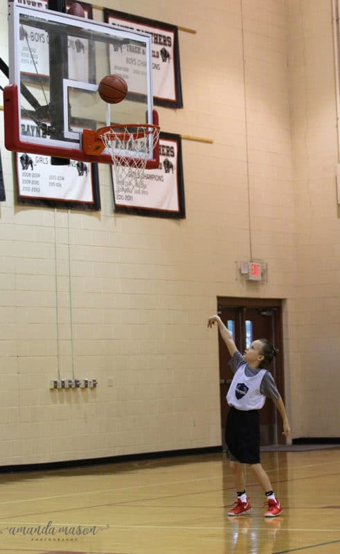 Boy shooting basketball into hoop in a gymnasium.