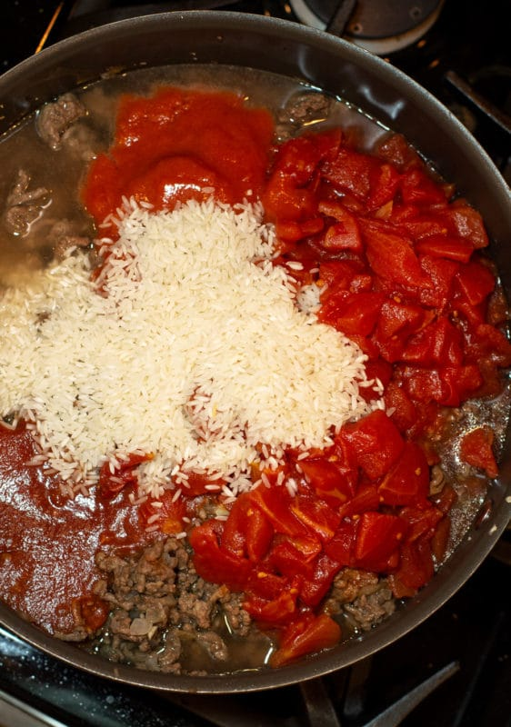 Pot containg diced tomatoes, tomato sauce, rice, and ground beef.