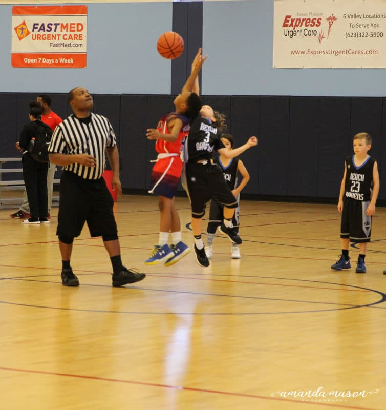 2 boys going for a jump shot during a basketball game.