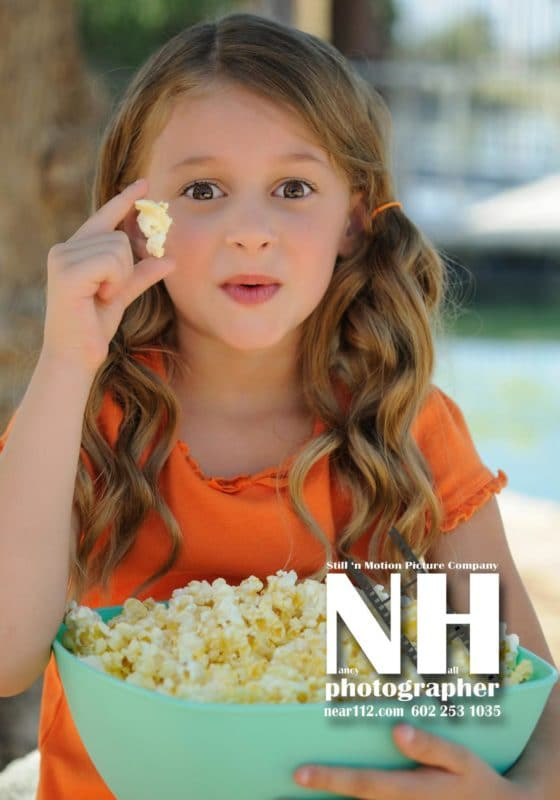 Kid female model holding a bowl of popcorn, kernel in hand.