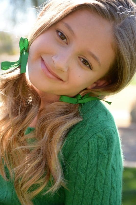 Kid female model with pigtails tied with green bows.