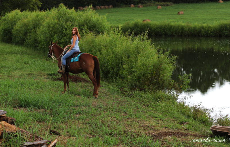 Girl on a horse on farm land, pond and hay in background.