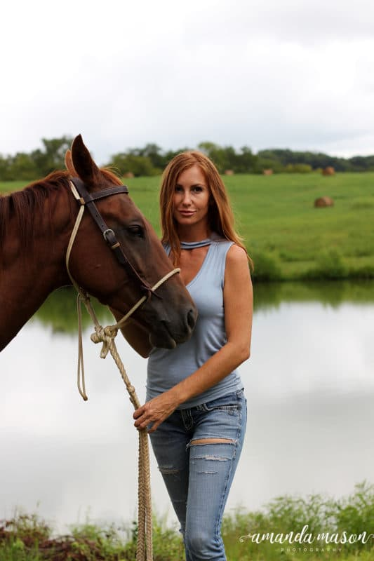 Girl holding the reigns of a horse on farm land, pond and hay in background.