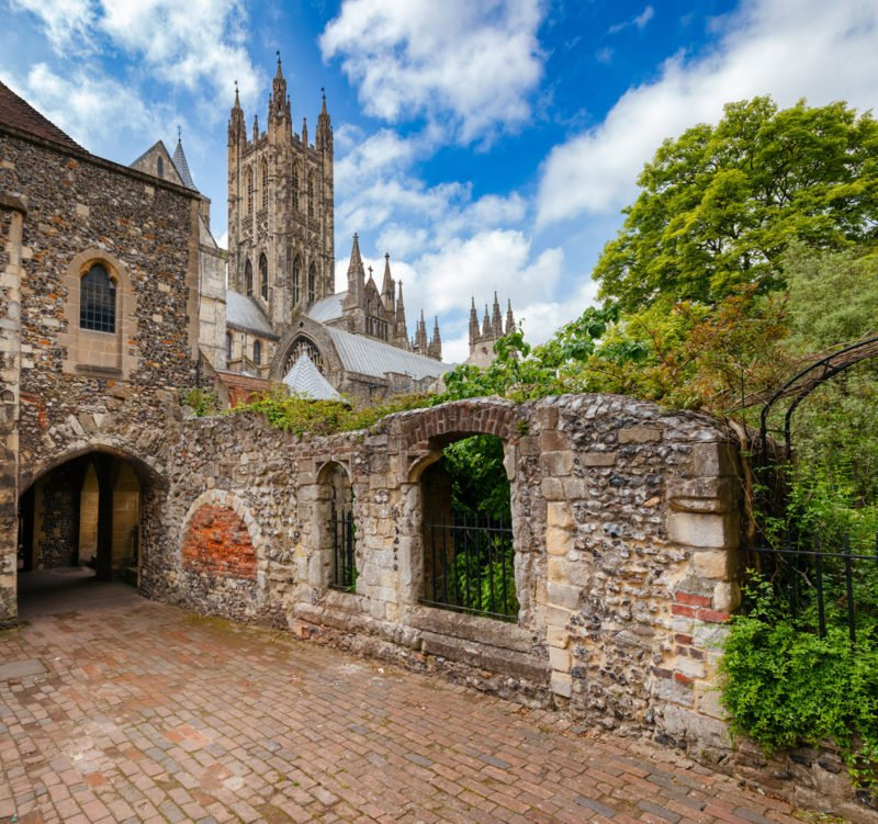 Canterbury Cathedral surrounded by a stone wall on a bright and sunny day.