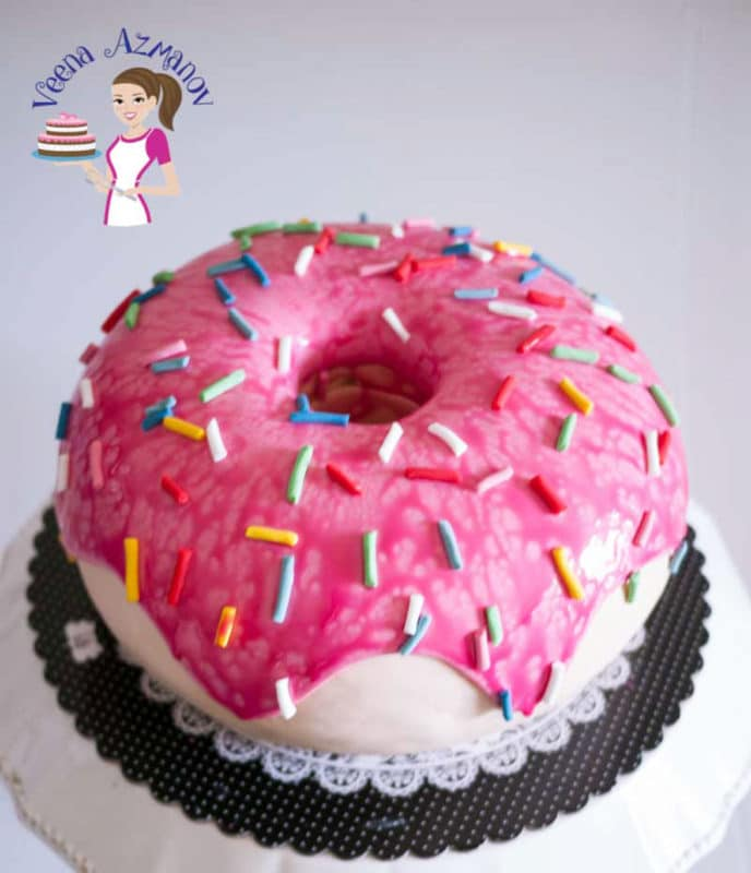 Pink donut cake topped with pink icing and colored sprinkles.