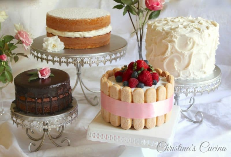 Display of 4 cakes: one chocolate, one white with berries and lady fingers, Once with white whipped frosting and a 2 tiered double cake.