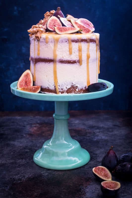3 tiered Honey Walnut Fig Cake sitting on a blue cake display topped with figs, honey dripping down cake.
