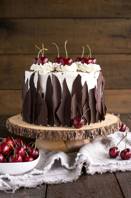 3 tiered Black Forest Cake topped with whipped cream and topped with cherries, bowl of red cherries on side.