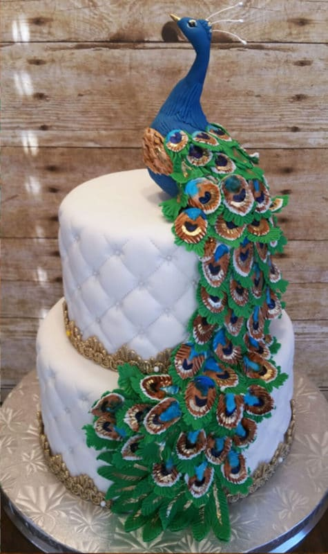 2 tiered white fondant cake topped with a blue peacock, icing feathers cascading down cake.