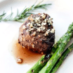 Grilled filet mignon topped with chopped garlic and rosemary, served with asparagus.
