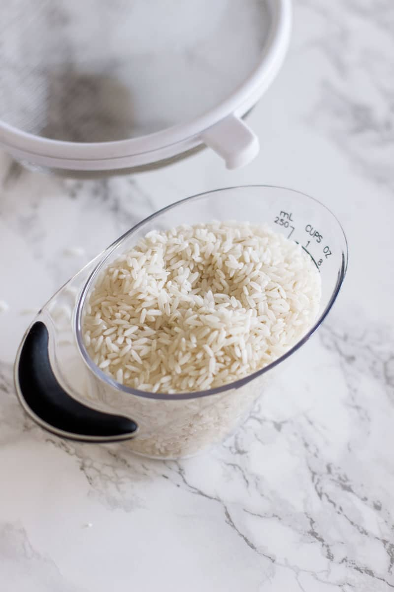 Measuring cup with 1 cup of rice filled.