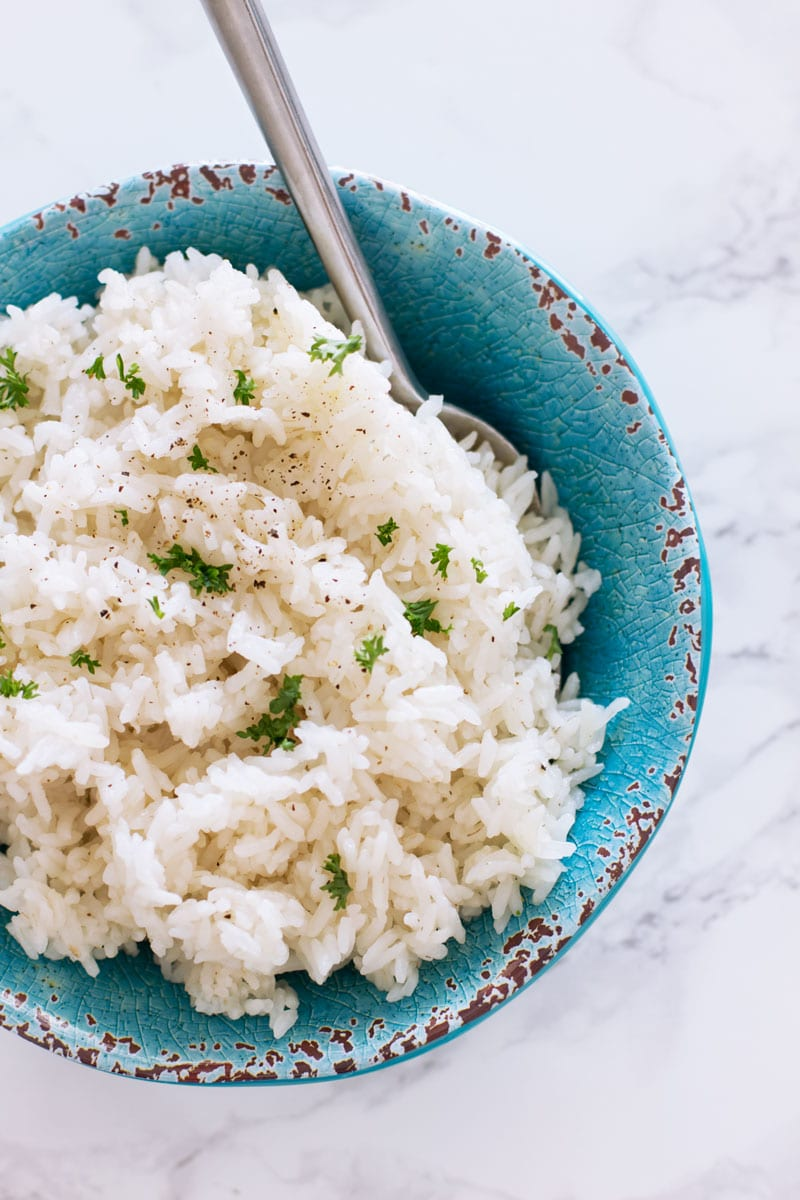 Bowl filled with instant pot white rice, spoon in bowl.