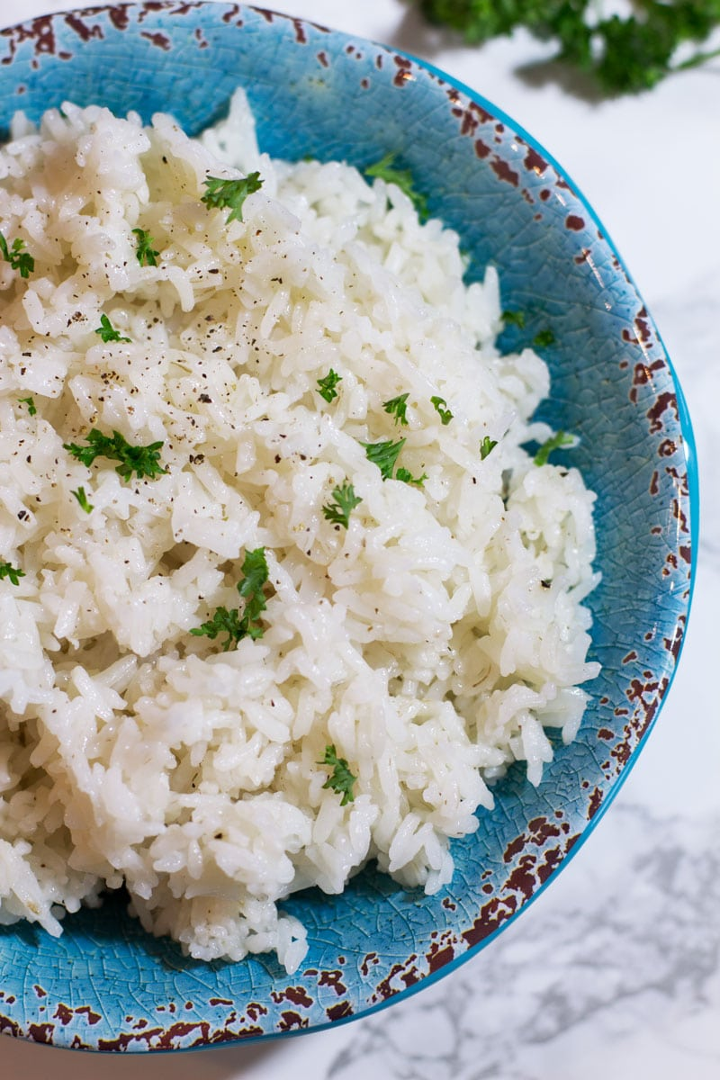 Blue bowl containing white rice made in the instant pot topped with pepper and fresh parsley.