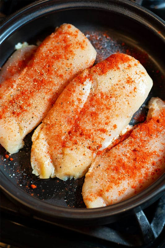 Three chicken breasts sprinkled with smoked Paprika, salt and pepper in a black pan.