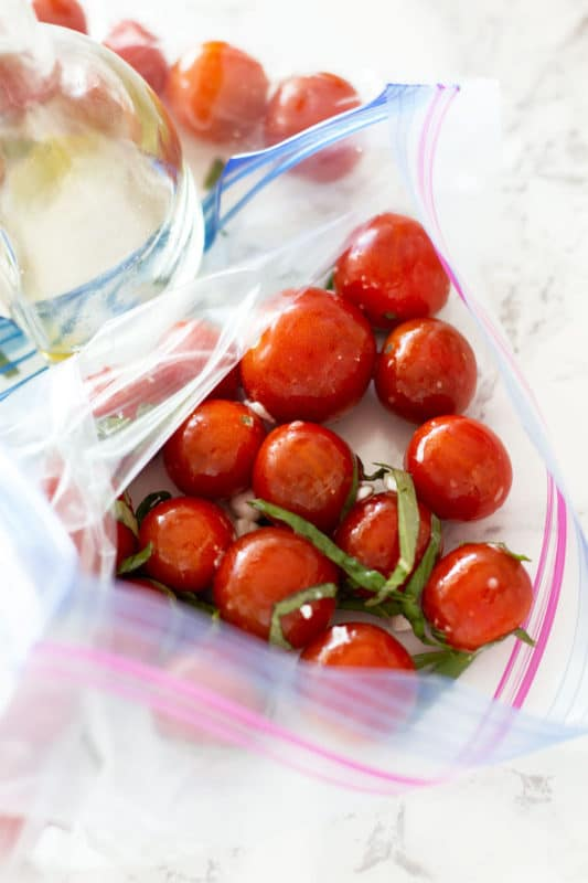 Ziplock bag containing cherry tomatoes with marinade.