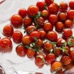 20 cherry tomatoes in marinade spread on piece of aluminum foil.