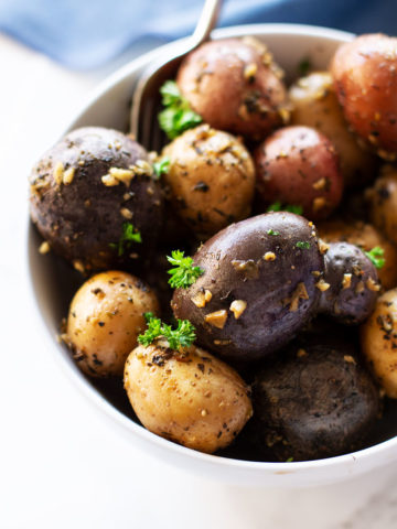 White bowl containing Garlic and Herb Smoked Potatoes topped with fresh parsley, spoon in bowl.