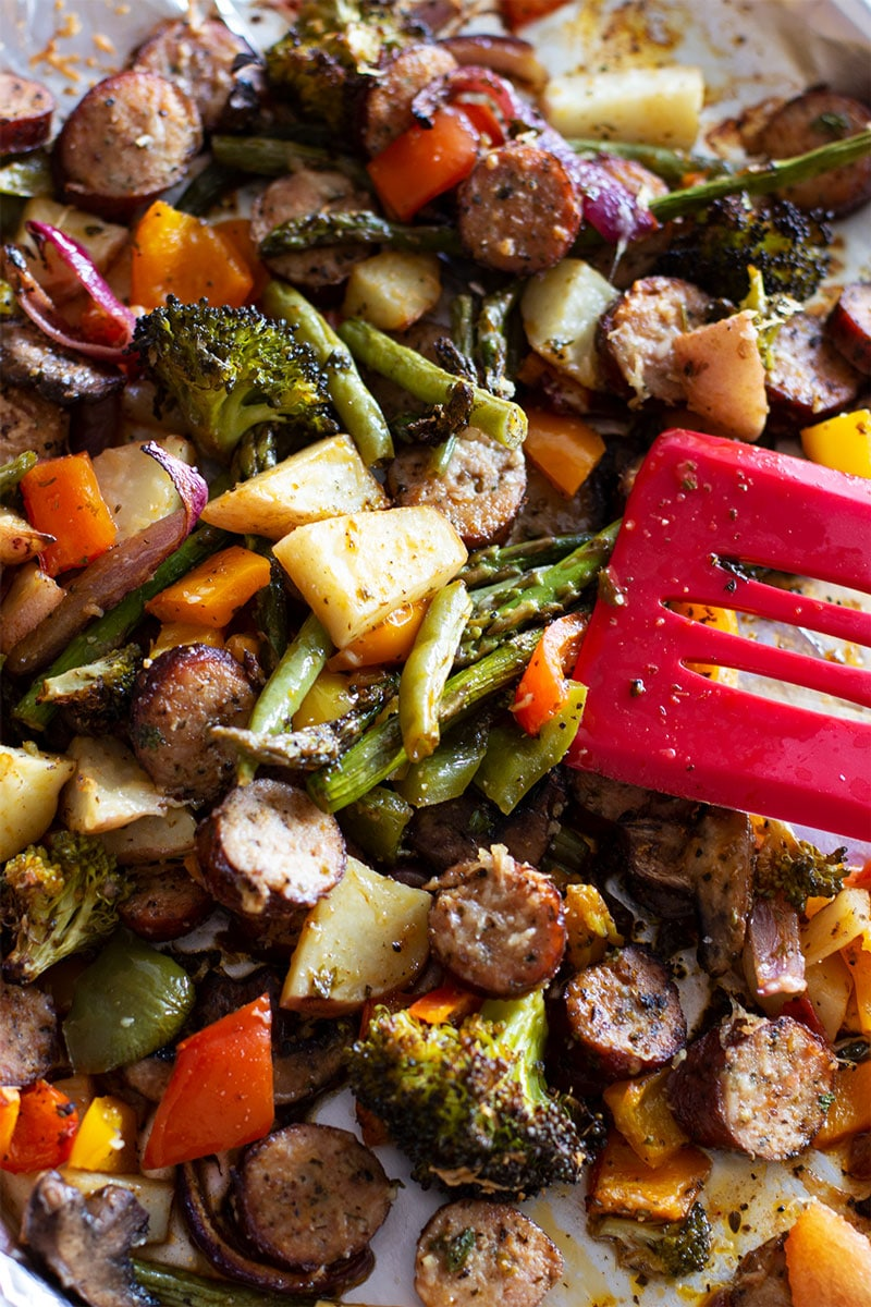 Cooked Asparagus, potatoes, broccoli, sausage and Smoked Sausage in a sheet pan.