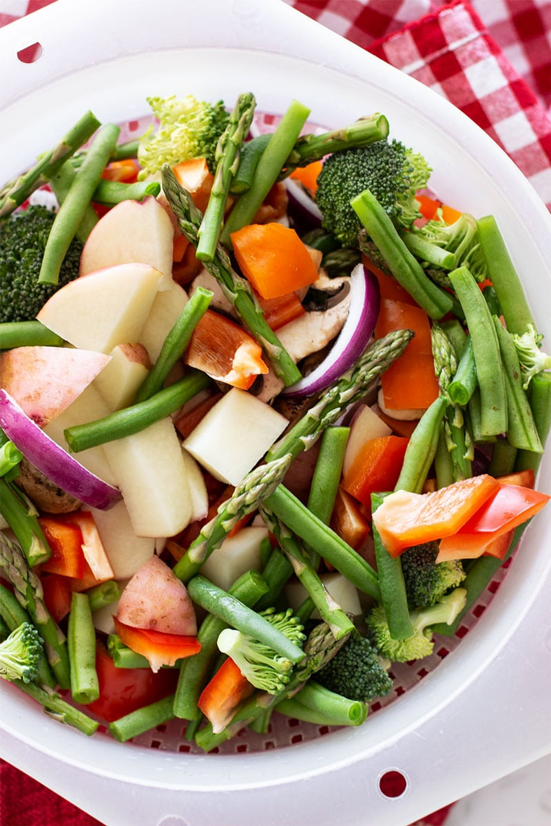Colander of fresh chopped vegetables containing asparagus, peppers, onions, broccoli and green beans.