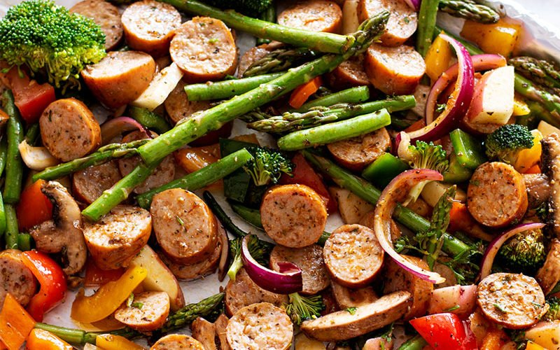 One Pan Smoked Sausage and Vegetables containing broccoli, asparagus, peppers, mushrooms and onion.